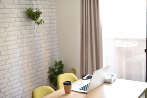 大きな窓のある書斎。テーブルにはノートパソコン。傍らにスターバックスのコーヒー